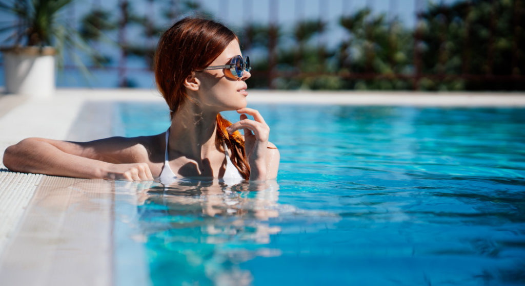 Woman at the edge of a swimming pool with sunglasses on