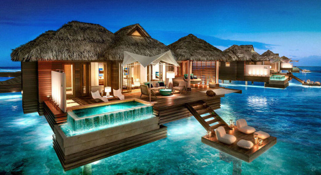 Overwater villa with pool at night in the Maldives