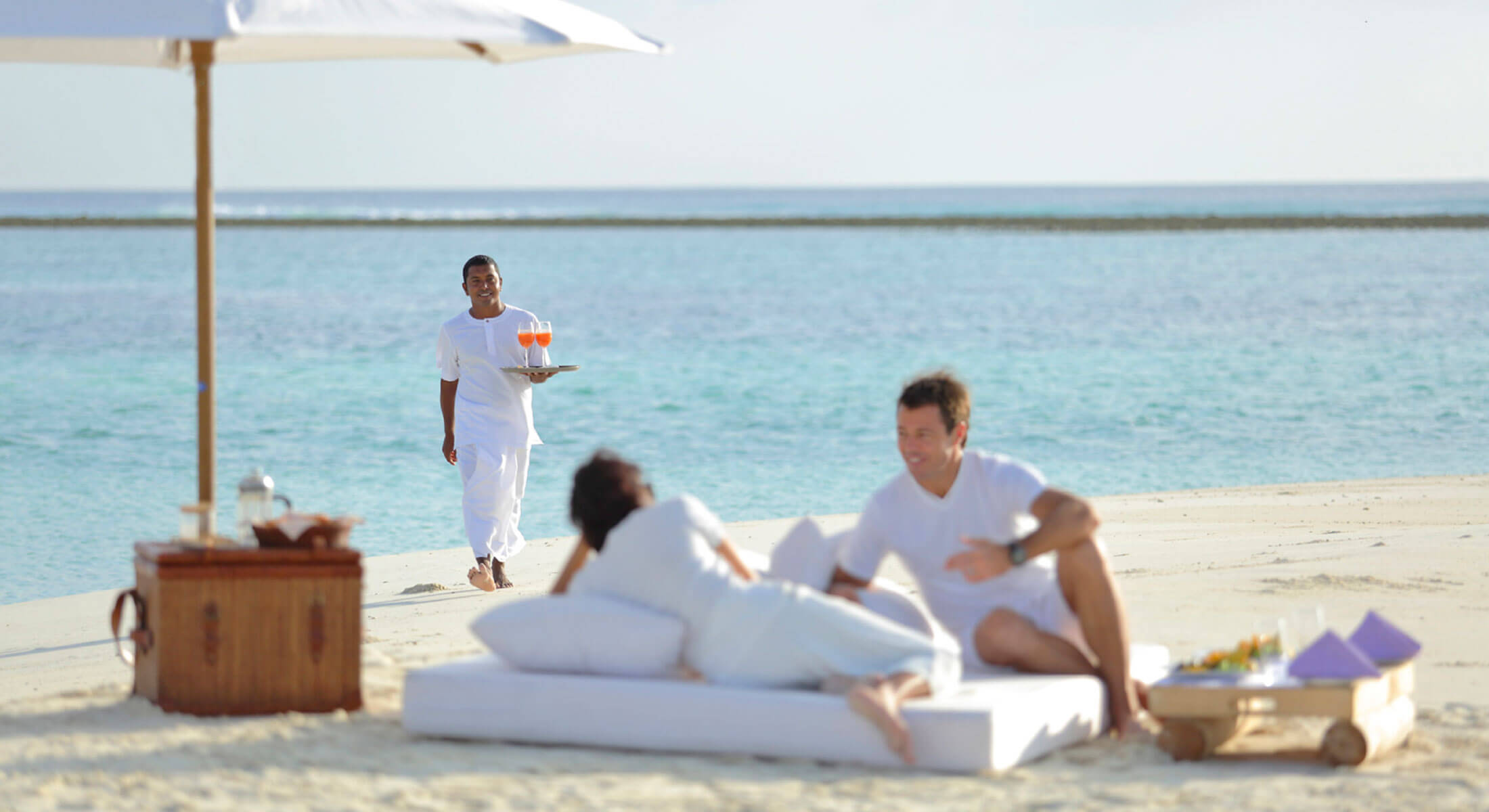 Couple in white laying on the beach being served by a Maldives waiter on their luxury holiday