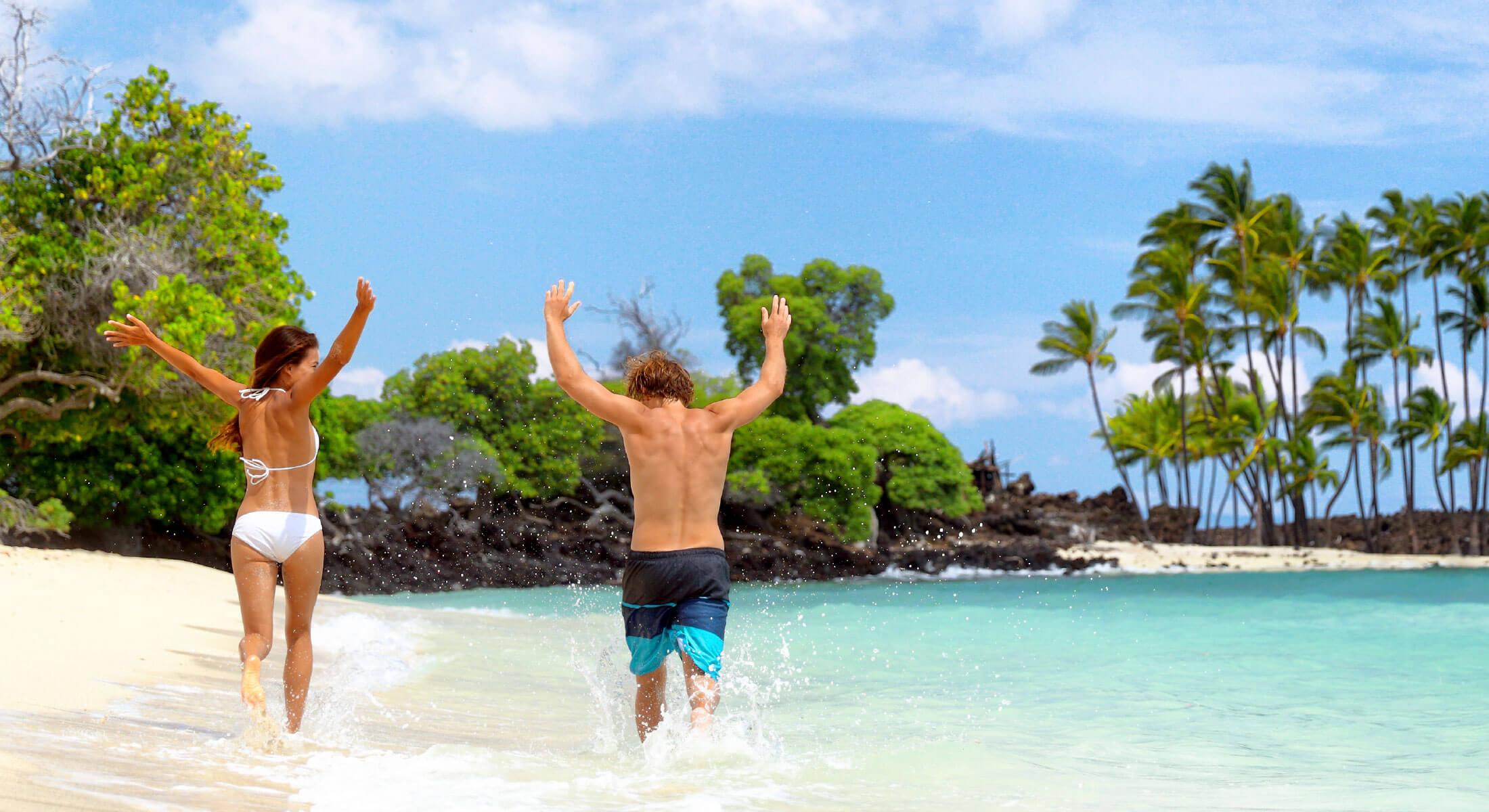 Couple splashing on a white sand beach