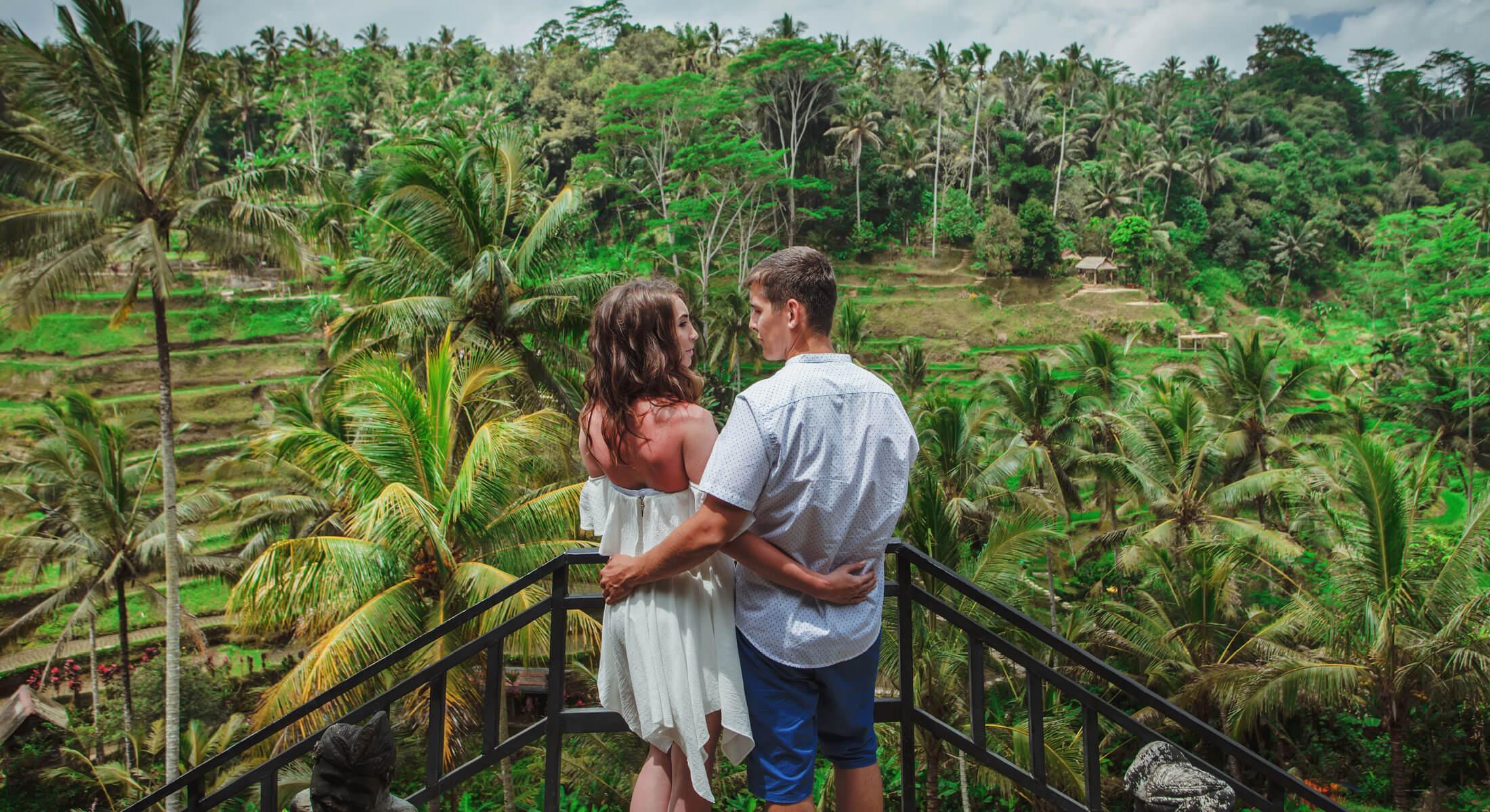 Couple on balcony overlooking rainforest