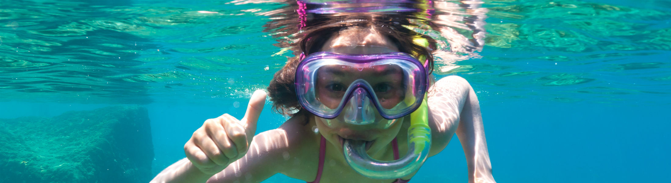 little girl with mask exploring underwater in the Mediterranean Sea