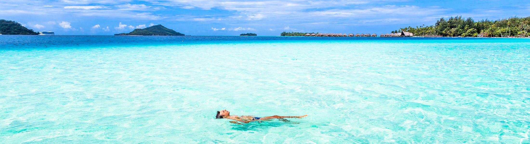 Man Swimming in blue waters in Bora Bora in the Pacific