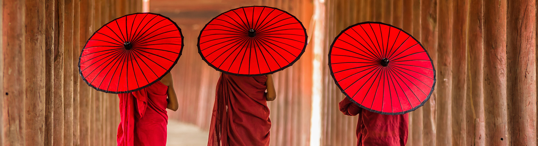 Buddhists with umbrellas walking in a pagoda in Myanmar