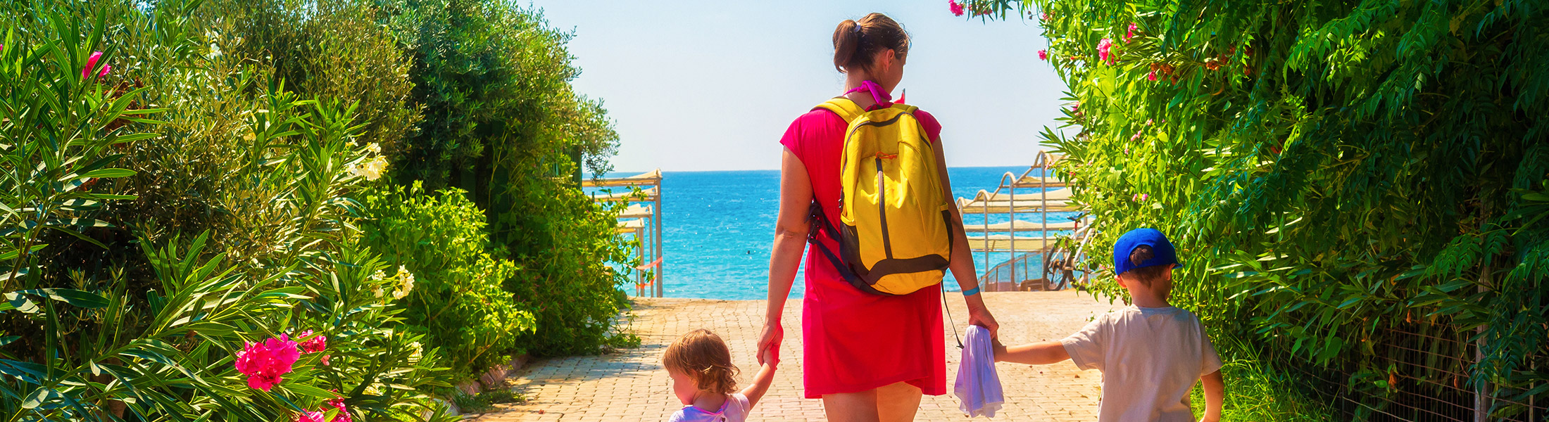 Mother and two children walking to the beach at Costa del Sol in Spain Europe