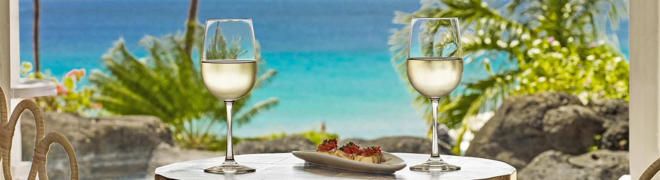 Wine glasses on a table overlooking the ocean in Barbados