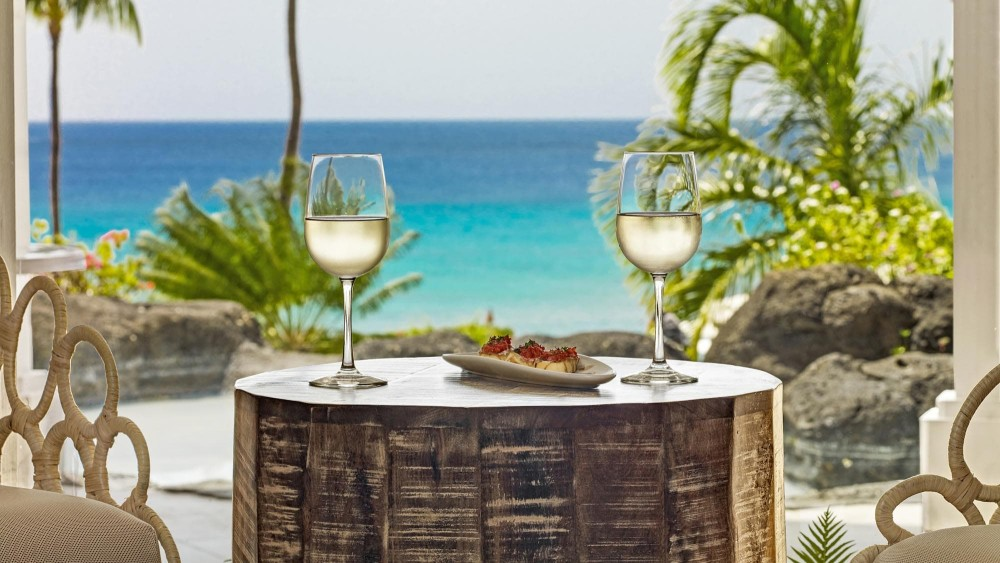 Wine glasses on a table overlooking the ocean at Crystal Cove by Elegant Hotels
