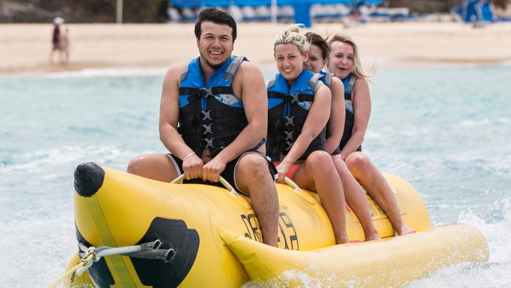 Young people enjoying riding an inflatable banana at Crystal Cove by Elegant Hotels