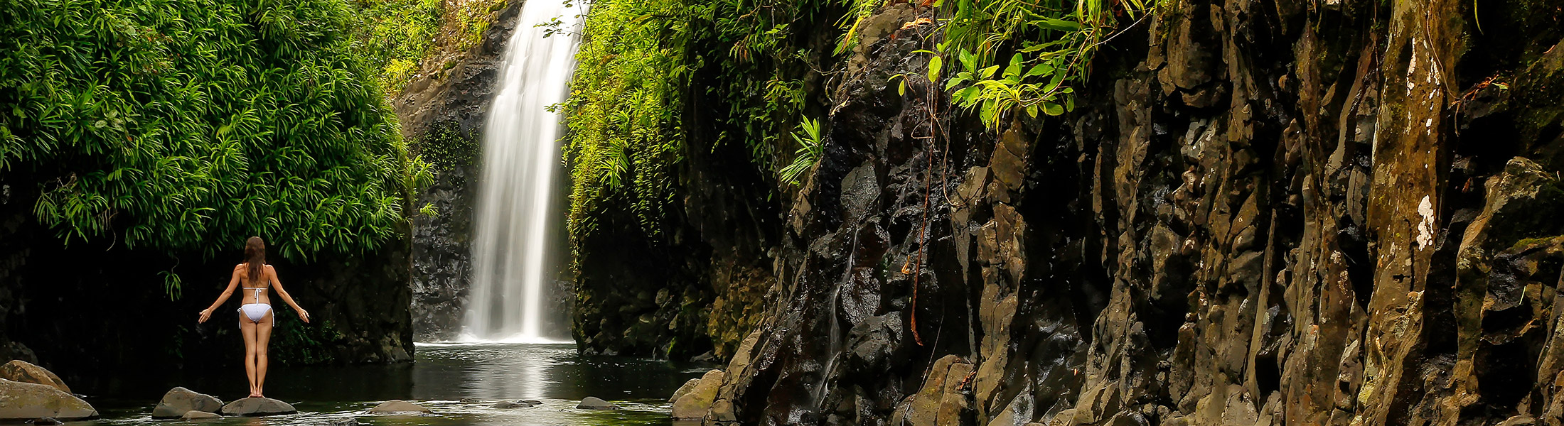 Woman at the base of a waterfall in Fiji in the Pacific