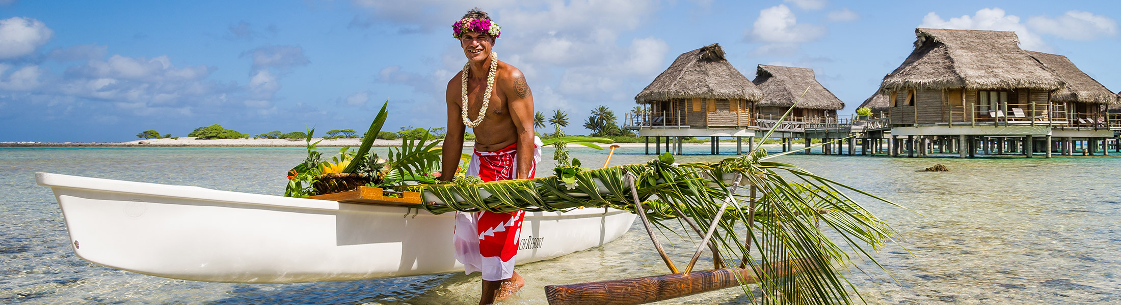 Traditional Pacific Island man pushing a boat in front of overwater villas in French Polynesia