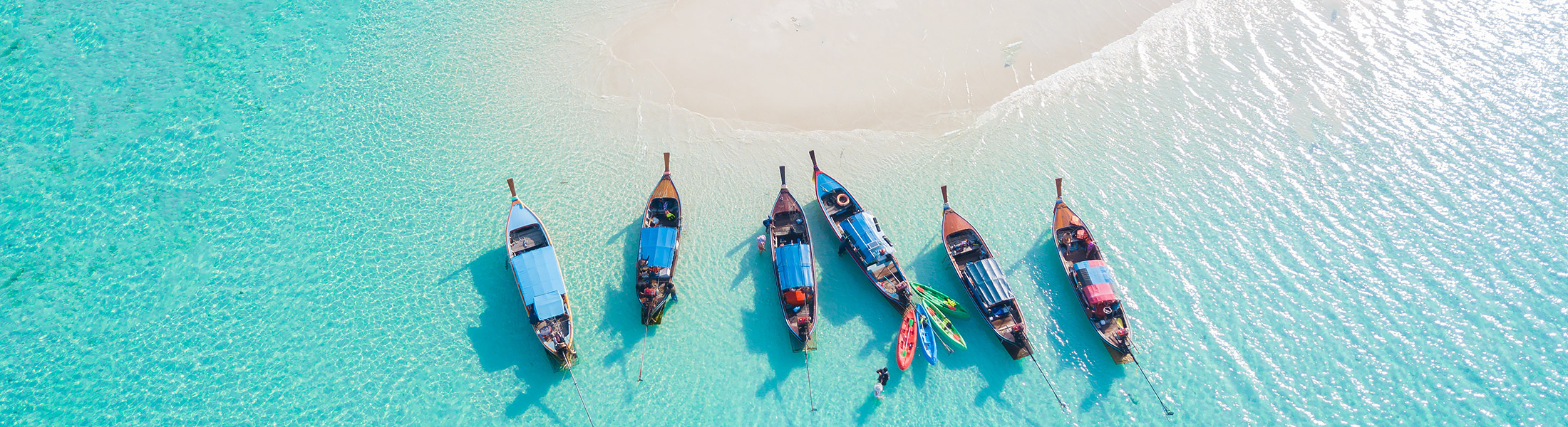 Longtail boats in blue water near a sandbar in Thailand