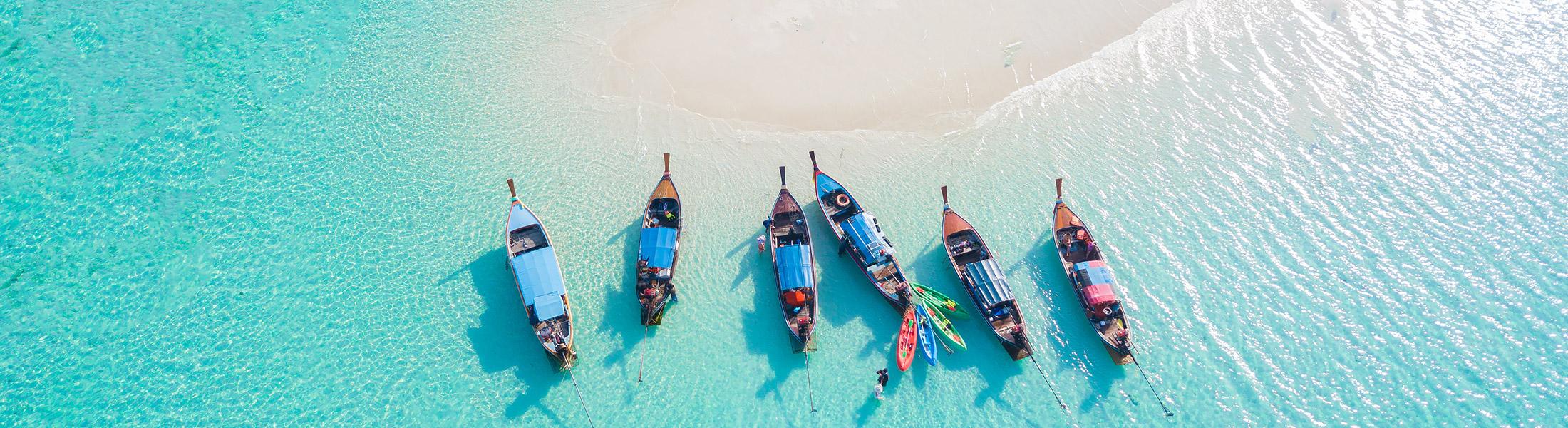 Longtail boats in blue water near a sandbar in Thailand