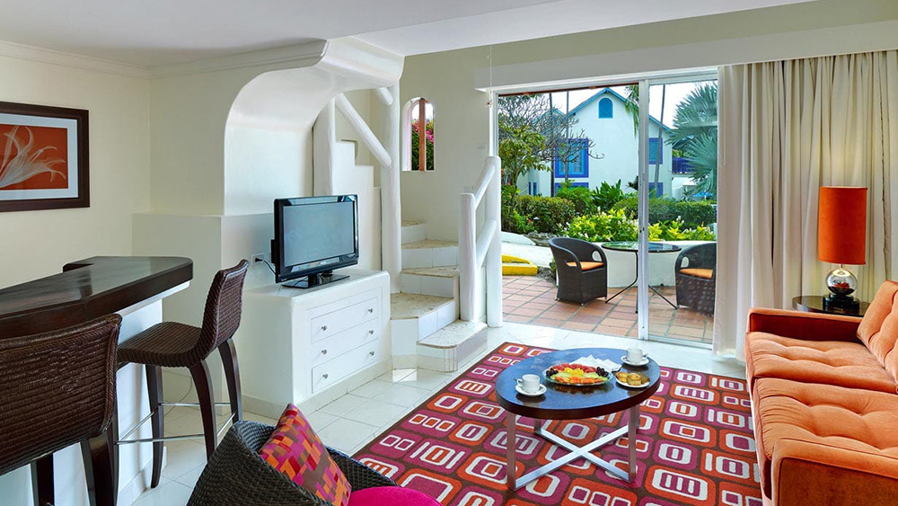 Living area and terrace in the One Bedroom Suite Garden View at Crystal Cove by Elegant Hotels