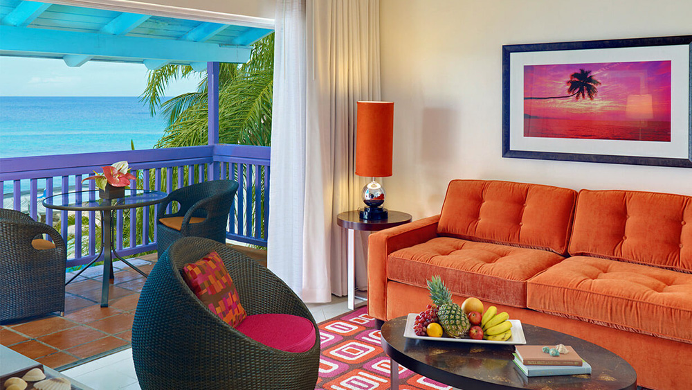 Living area and balcony of the One Bedroom Suite Ocean View at Crystal Cove by Elegant Hotels
