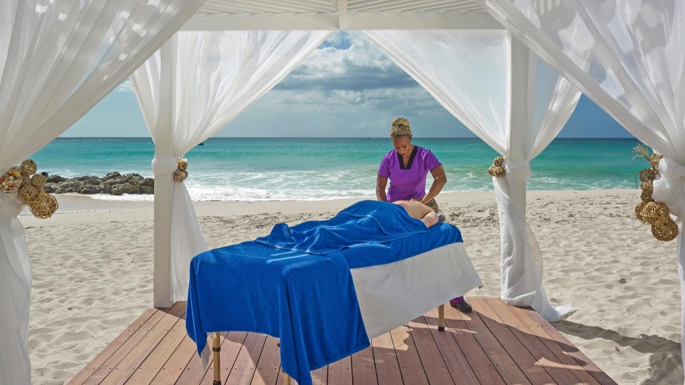 Woman receiving a massage from a therapist at Crystal Cove by Elegant Hotels
