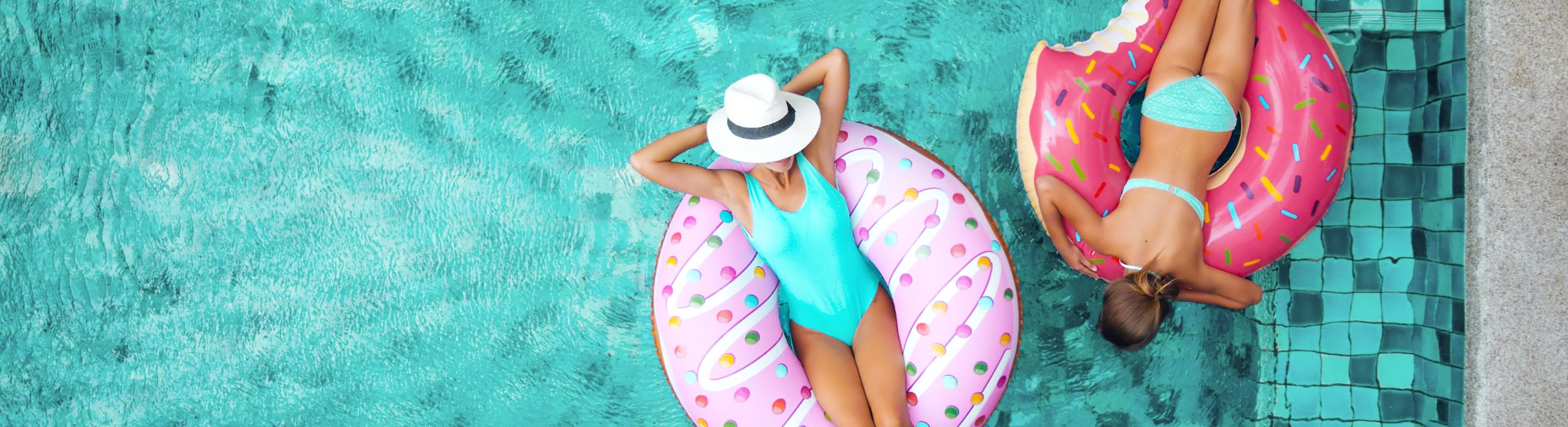 Woman on pool floats in their villa pool