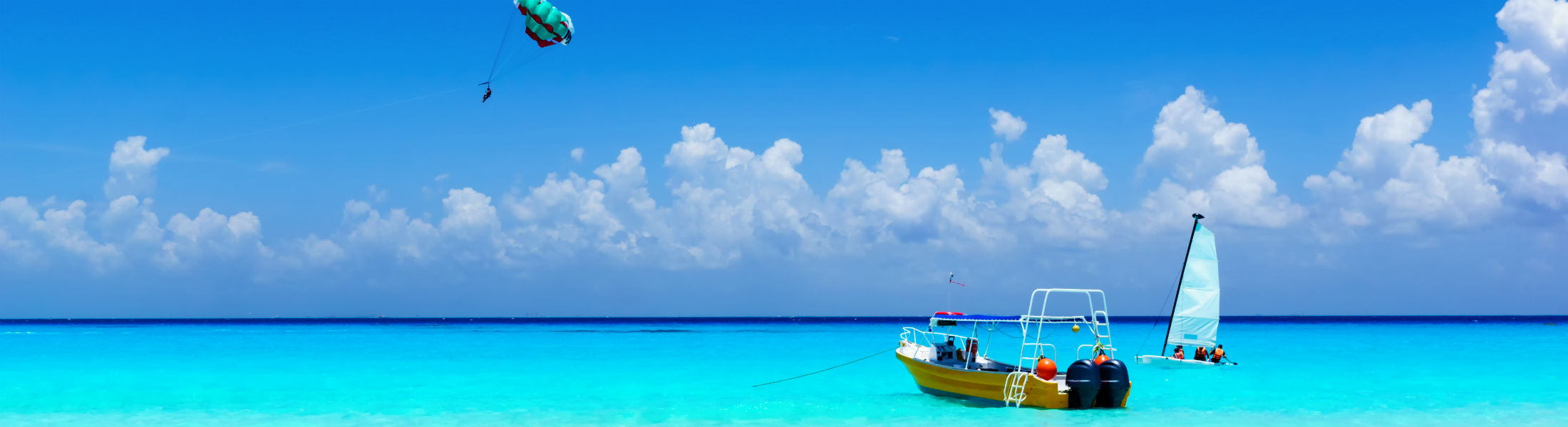 Parasailing in a blue sky waters in the Cancun