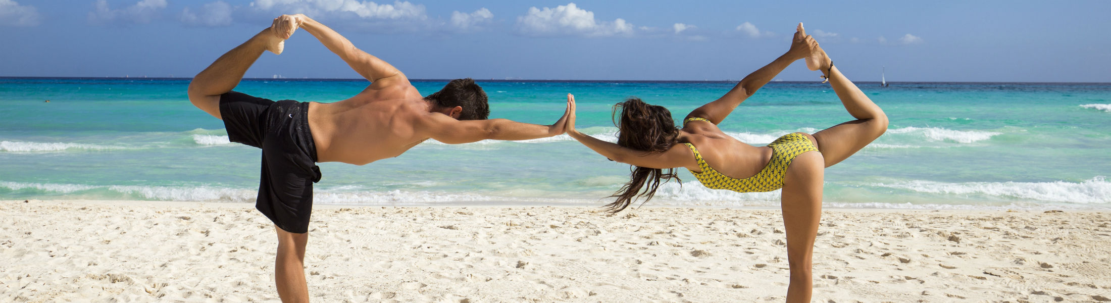 Couple doing yoga at the beach in their swimwear