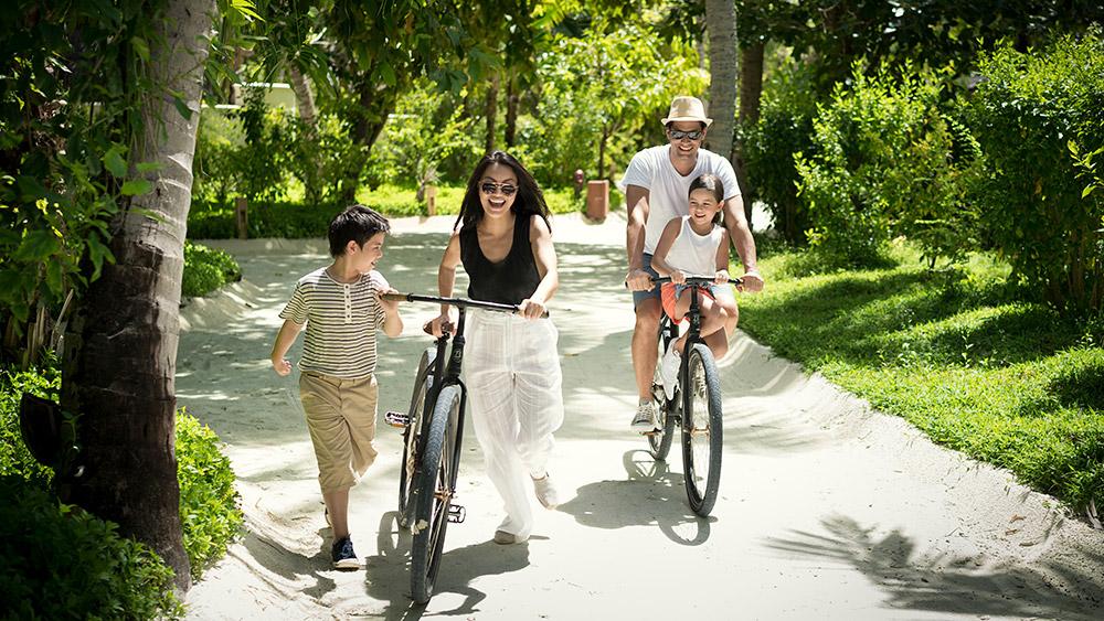 Family riding bikes at Anantara Dhigu Resort