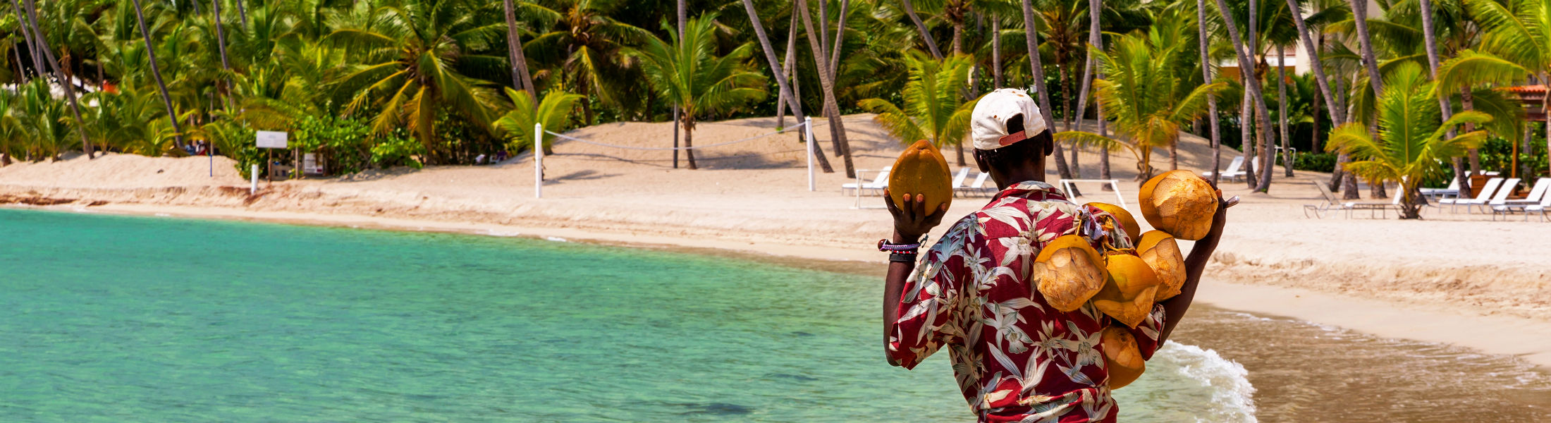 Coconut saler walking by the sea in the famous Juan Dolio Beach of Dominican Republic