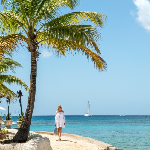 Woman walking on the beach at Coral Reef Club