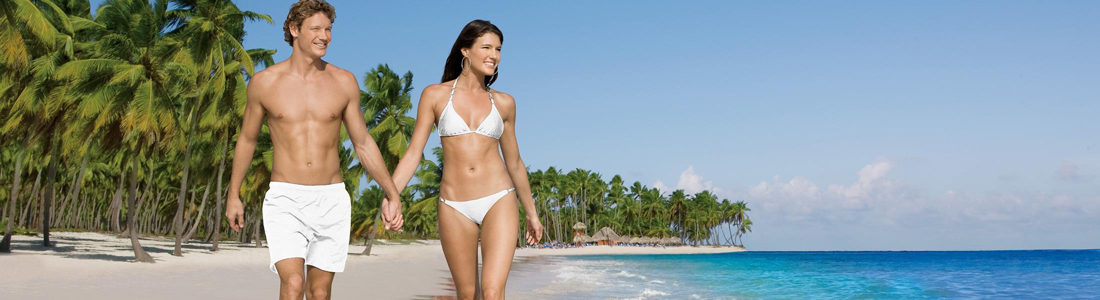 Couple walking long hotel beach at the Dreams Palm Beach Punta Cana