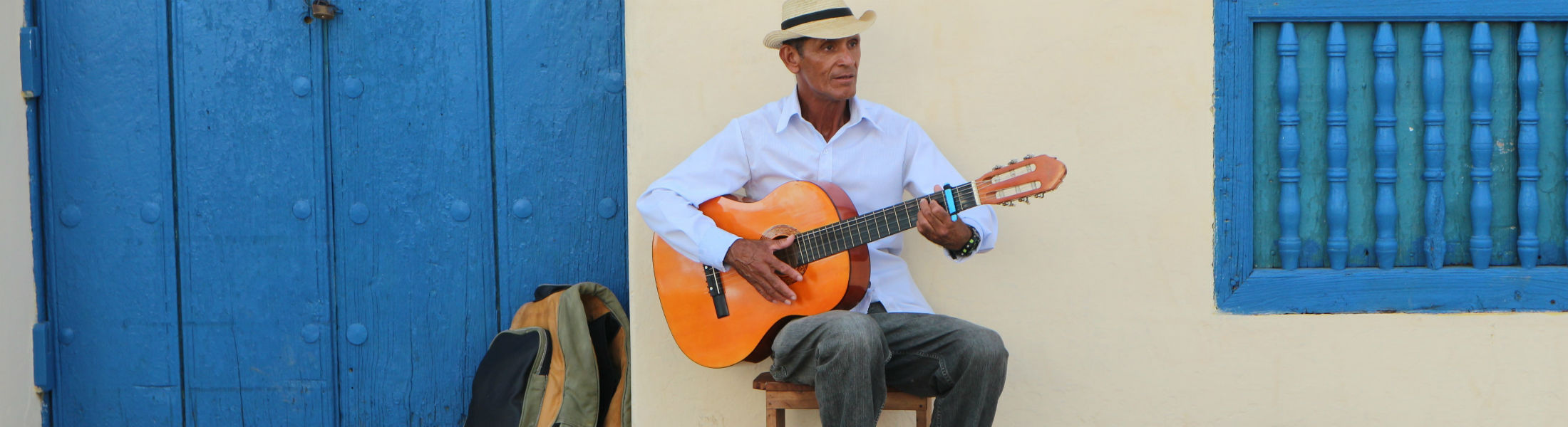 Cuban man wearing traditional panama straw hat playing an acoustic guitar_