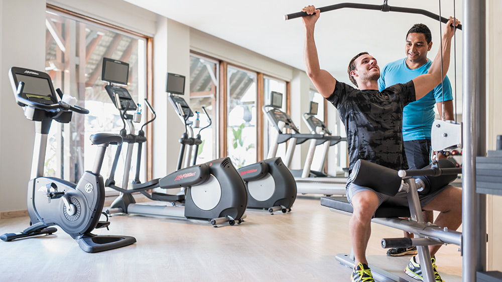 Man and personal trainer in a gym at Shangri-La's Le Touessrok Mauritius