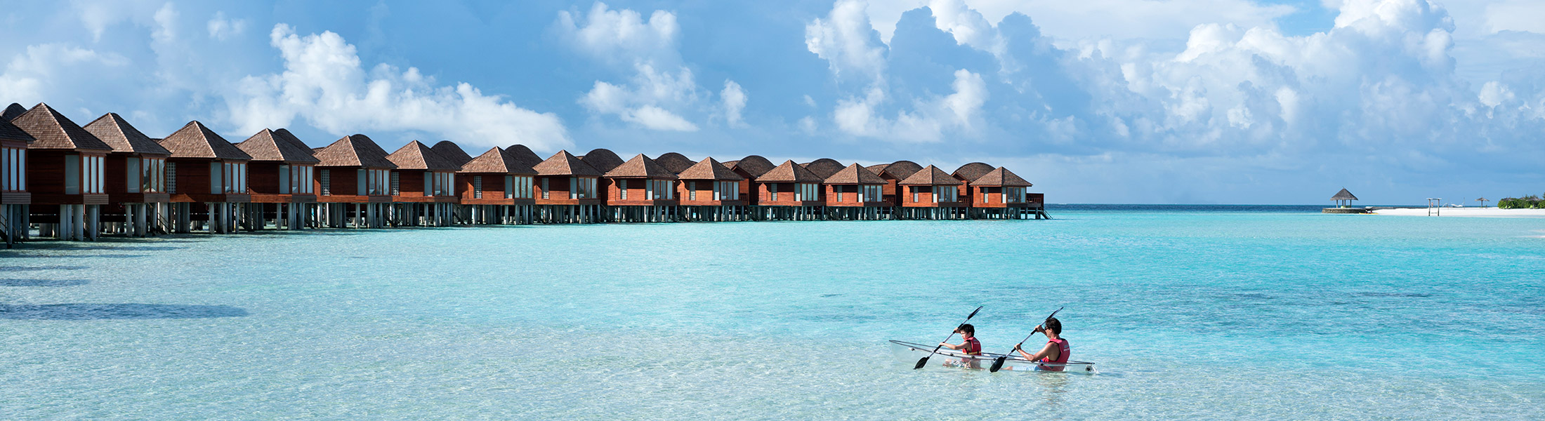 Couple kayaking in front of over water villas at Anantara Dhigu Resort
