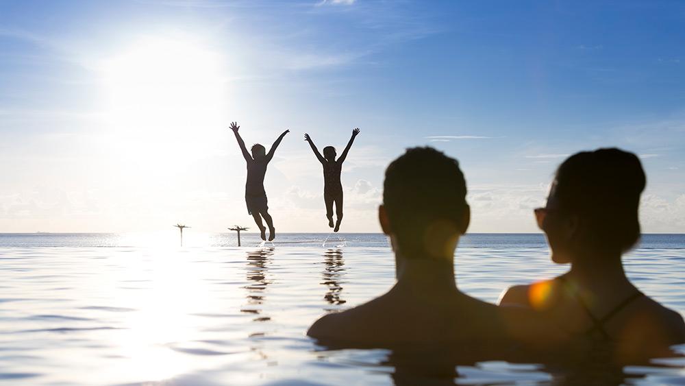 Family in the infinity pool at Anantara Dhigu Resort