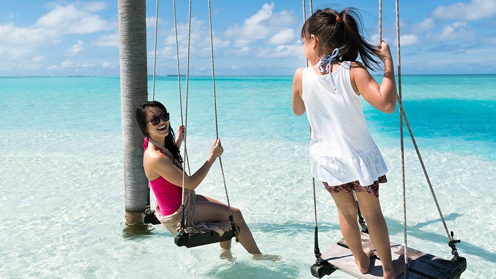 Mother & Daughter on a swing in the blue ocean at Anantara Dhigu Resort