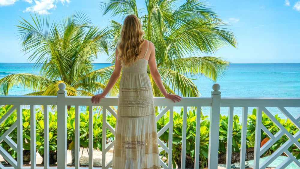 Woman looking from balcony at Coral Reef Club in Barbados