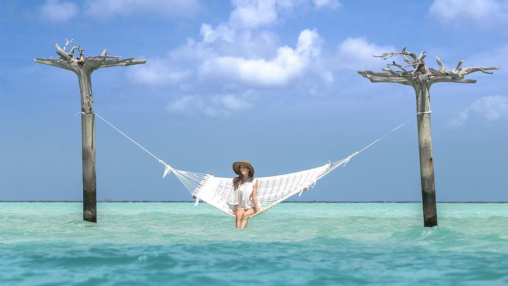 Wman on a hamoock over the blue ocean at Anantara Dhigu Resort