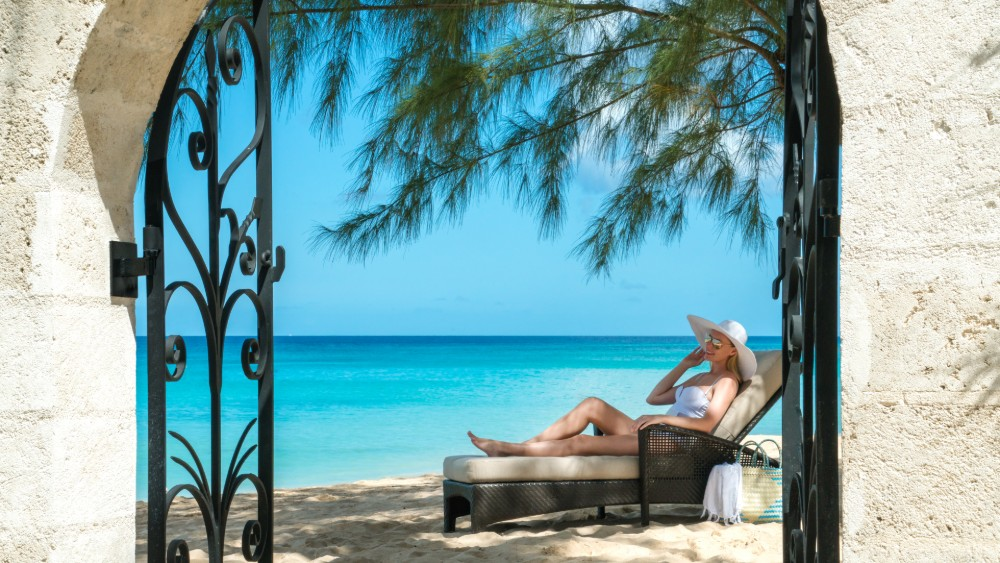 Woman on a sun lounger at Coral Reef Club in Barbados