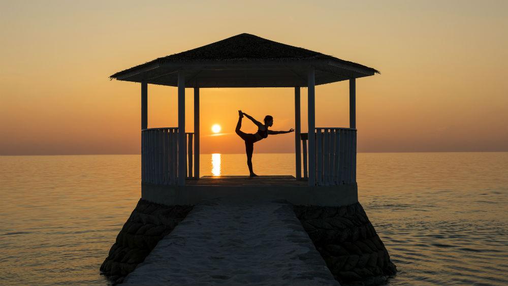 Woman doing yoga in a pavilion at sunset at Centara Ras Fushi Resort & Spa
