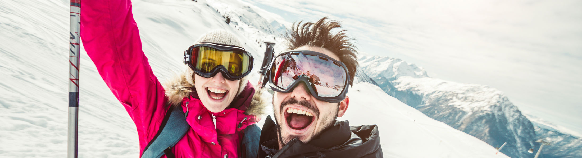 skier couple taking a selfie in the snow on a mountain