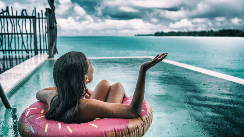 Woman in a pool while it's raining in the Maldives