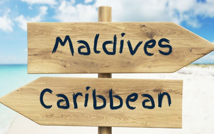 Caribbean and Maldives on beach sign posts
