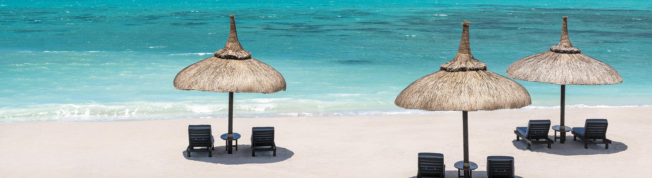 Sun lounges and umbrellas on the beach at Shangri-La's Le Touessrok Mauritius
