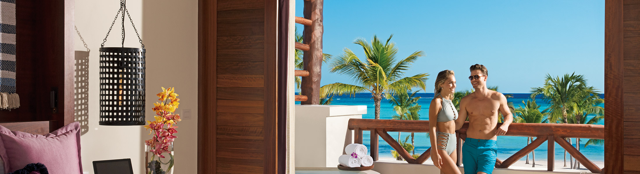 Couple on the balcony of their suite at Secrets Cap Cana Resort & Spa
