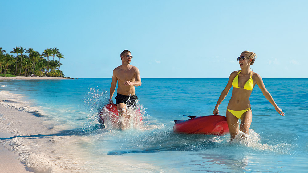 Couple with paddle boards at Secrets Cap Cana Resort & Spa in Dominican Republic