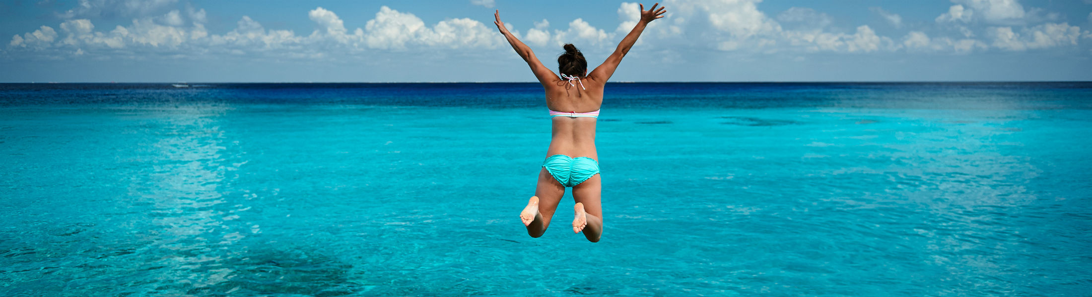 Woman jumping in blue water in tropical sea water