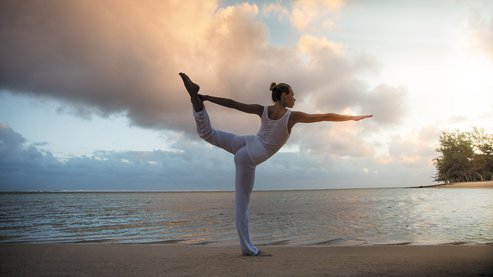 Woman doing yoga on the beach at Heritage Le Telfair Mauritius
