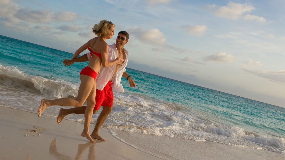 couple running on the beach at the Turtle Beach by Elegant Hotels