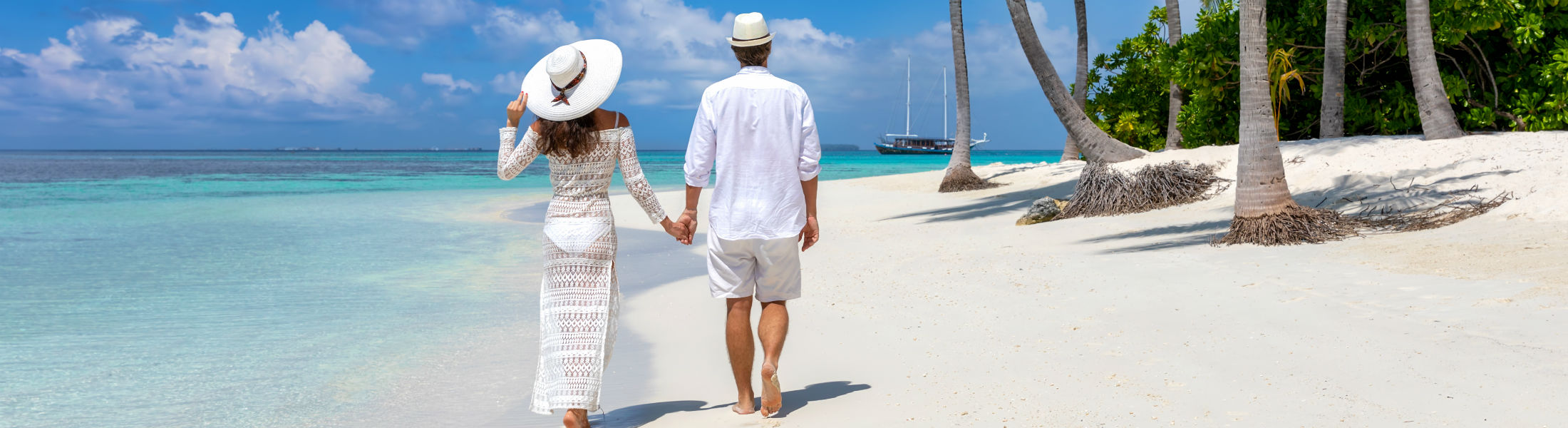 couple walks down a tropical beach