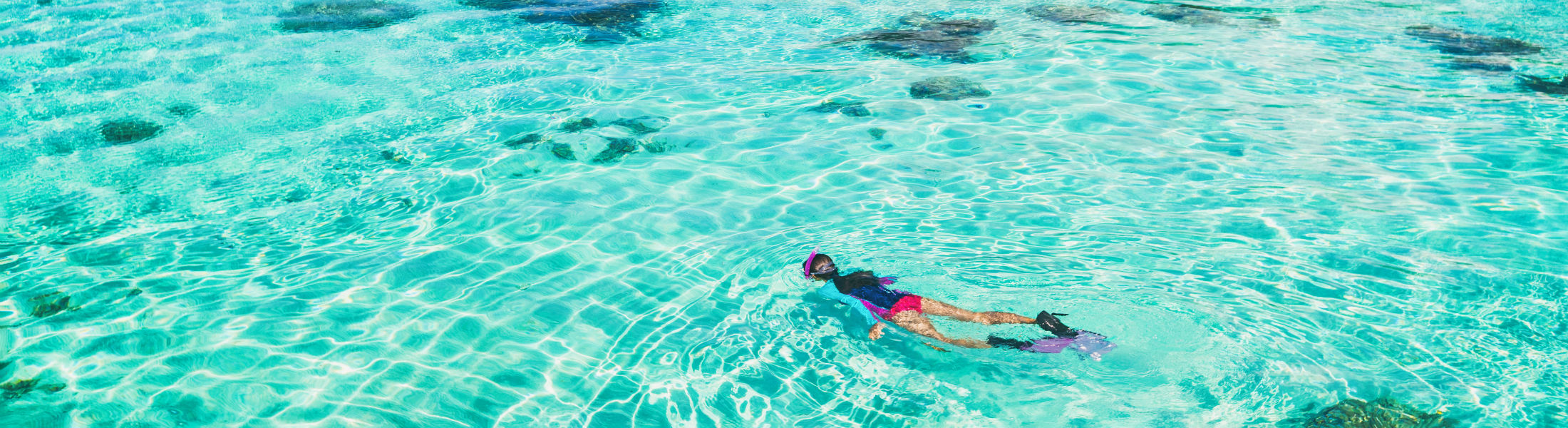 woman swimming snorkelling in paradise clear water