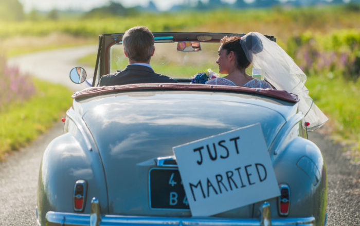 A newlywed couple is driving