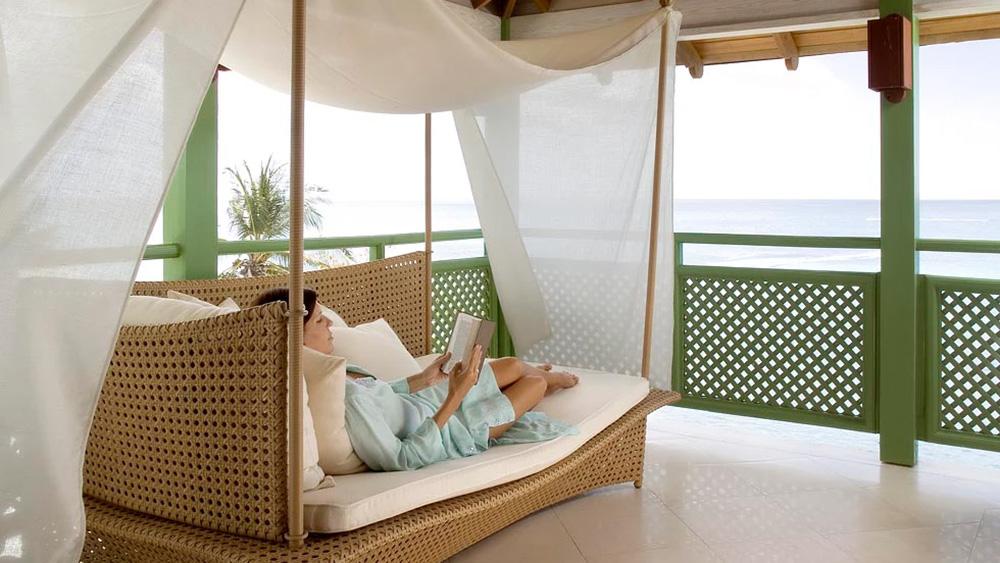 Woman reading on the balcony at Mango Bay