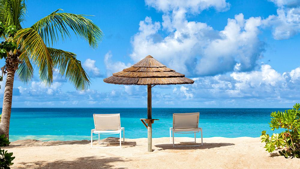 sun loungers under an umbrella at the beach at Galley Bay Resort & Spa