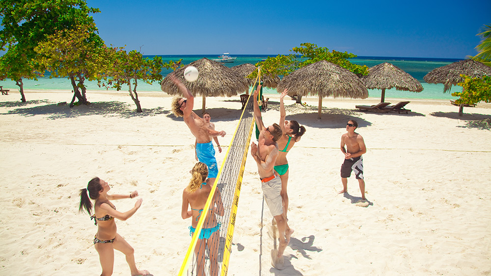 People playing beach volleyball at Sandals Montego Bay